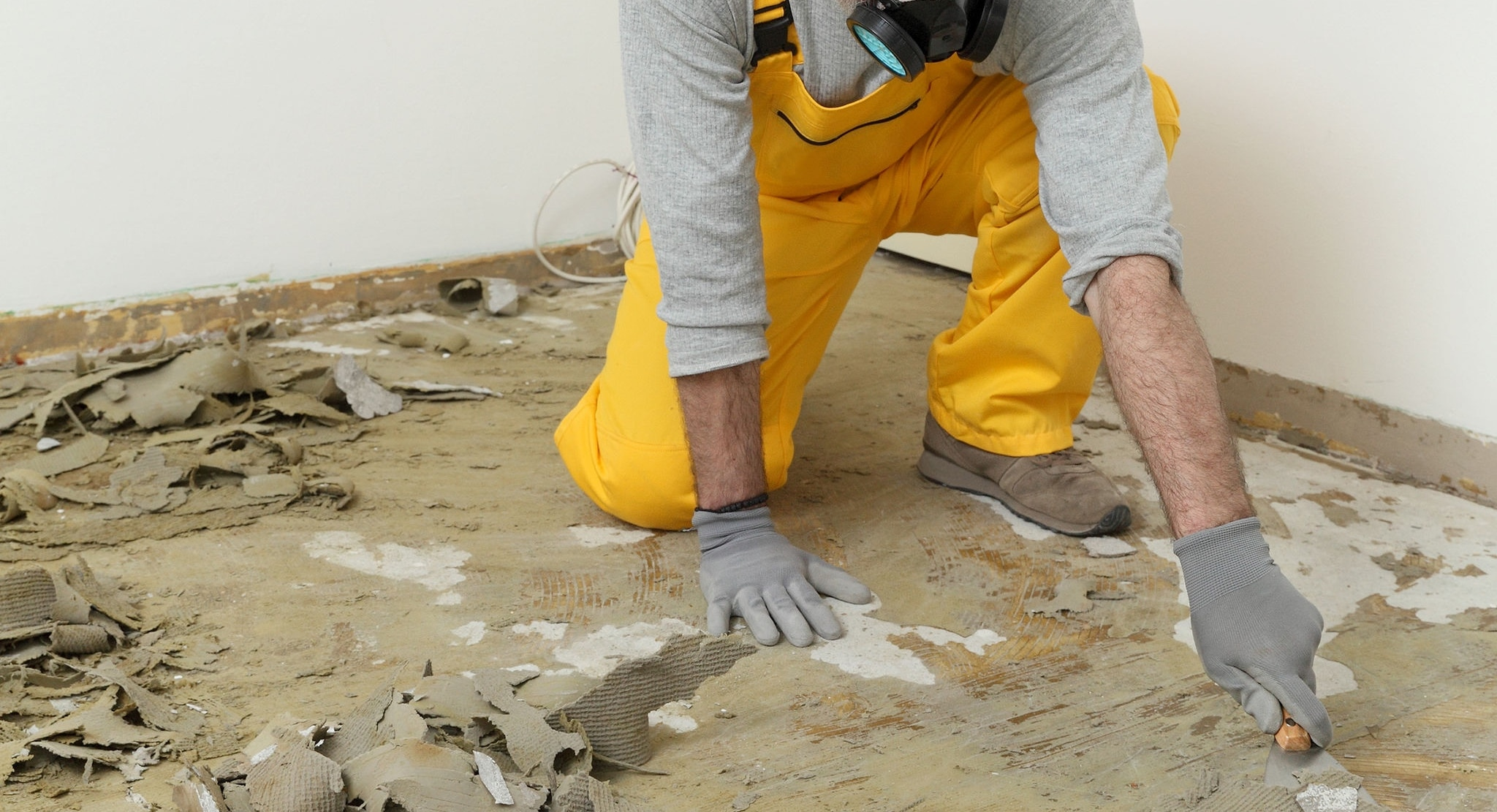 Adult worker with protective mask remove glue and rubber with putty knife from floor